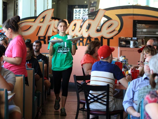 Amy Ball delivers plates to waiting diners at the Arcade