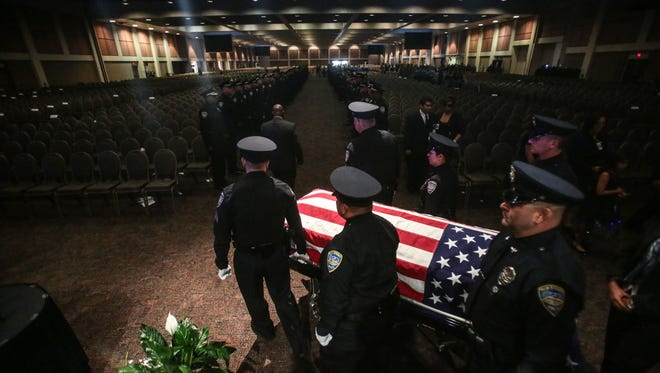 """The body of fallen Palm Springs Police Officer Jose """"Gil"""" Vega is taken from the Palm Springs Convention Center to his funeral after his memorial service on Oct. 18, 2016."""