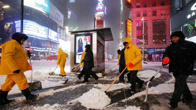 A crew of snow shovelers work as a snowstorm sweeps through Times Square, Tuesday, March 14, 2017, in New York.