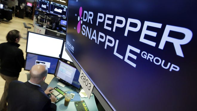 The Dr Pepper Snapple Group logo appears above a trading post on the floor of the New York Stock Exchange on Monday, Jan. 29, 2018. Keurig is buying Dr Pepper Snapple Group Inc., creating a beverage giant with about $11 billion in annual sales.