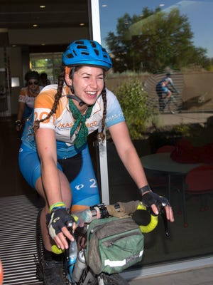 Texas 4000 bicyclist Katie Russell rides through the San Juan Regional Cancer Center in Farmington on Wednesday before the members of her group left for their next stop in Utah.