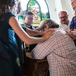 The Rev. Scott Oxford leads a laying on of hands prior to a recent Wednesday evening service.