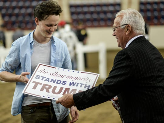 Elan Stuzfoltz, a Lancaster resident and volunteer for the Trump Campaign, hands out signs before the start of Donald Trump's campaign rally at the Pennsylvania Farm Show Complex in Harrisburg on April 21, 2016.