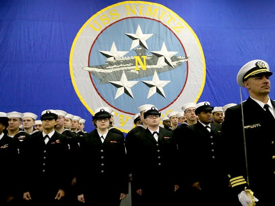 Nimitz sailors stand at attention in front of their ship's flag during Thursday's change-of-command ceremony aboard the USS Nimitz at Naval Base Kitsap-Bremerton.