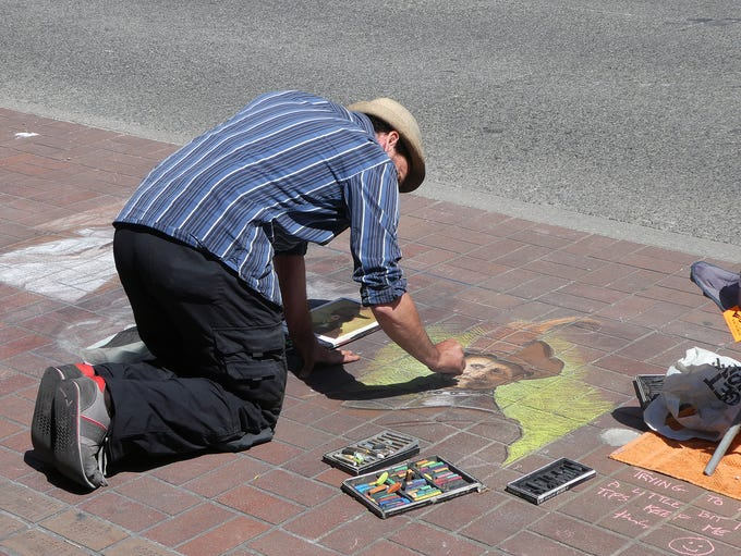 A street artist paints with chalk in downtown Victoria,