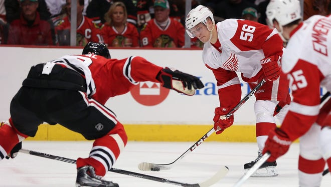 Teemu Pulkkinen of the Detroit Red Wings looks to shoot against Michal Rozsival of the Chicago Blackhawks on March 16, 2014, in Chicago.