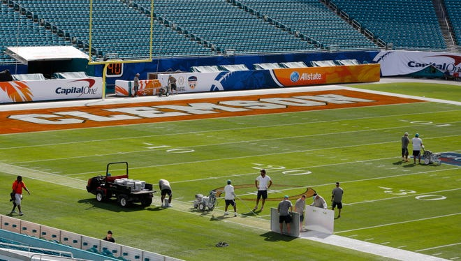 Workers prepare for the Orange Bowl game in Miami Gardens, Fla., in 2015.