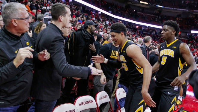 Iowa's Cordell Pemsl (35) and Tyler Cook (5) celebrate the team's 59-57 win over Wisconsin in Madison.