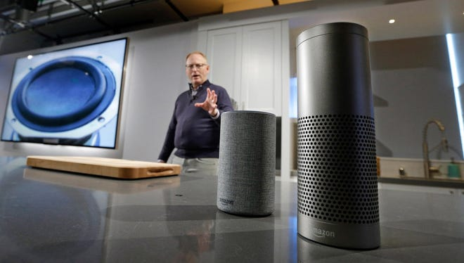 "David Limp, senior vice president of Devices and Services at Amazon, displays a new Echo, left, and an Echo Plus during an event announcing several new Amazon products by the company, Wednesday, Sept. 27, 2017, in Seattle. Amazon says it is cutting the price of its Echo smart speaker, improving the sound quality and upgrading its appearance with six new ""shells."" The online retailer also announced a premium version of the Echo Plus, which has improved sound and can act as the hub of a smart home."