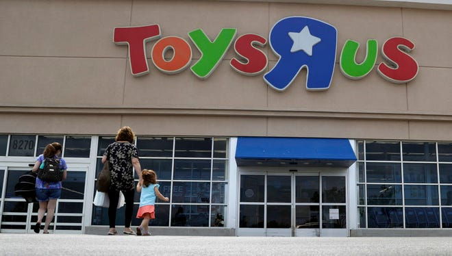 FILE - In this Sept. 19, 2017, file photo, shoppers walk into a Toys R Us store, in San Antonio. Toys R Us says it will be closing some U.S. stores and converting others to cobranded locations as it continues to deal with its financial restructuring following its bankruptcy filing.