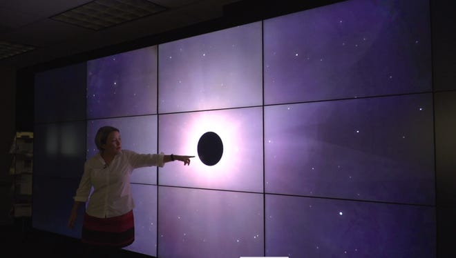 NASA scientist Aki Roberge pointing to a graphic of a planet blocking part of a star.