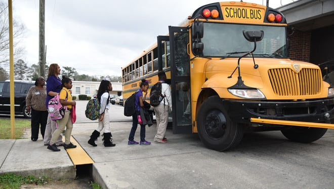 Students in the Hattiesburg School District board a school bus.