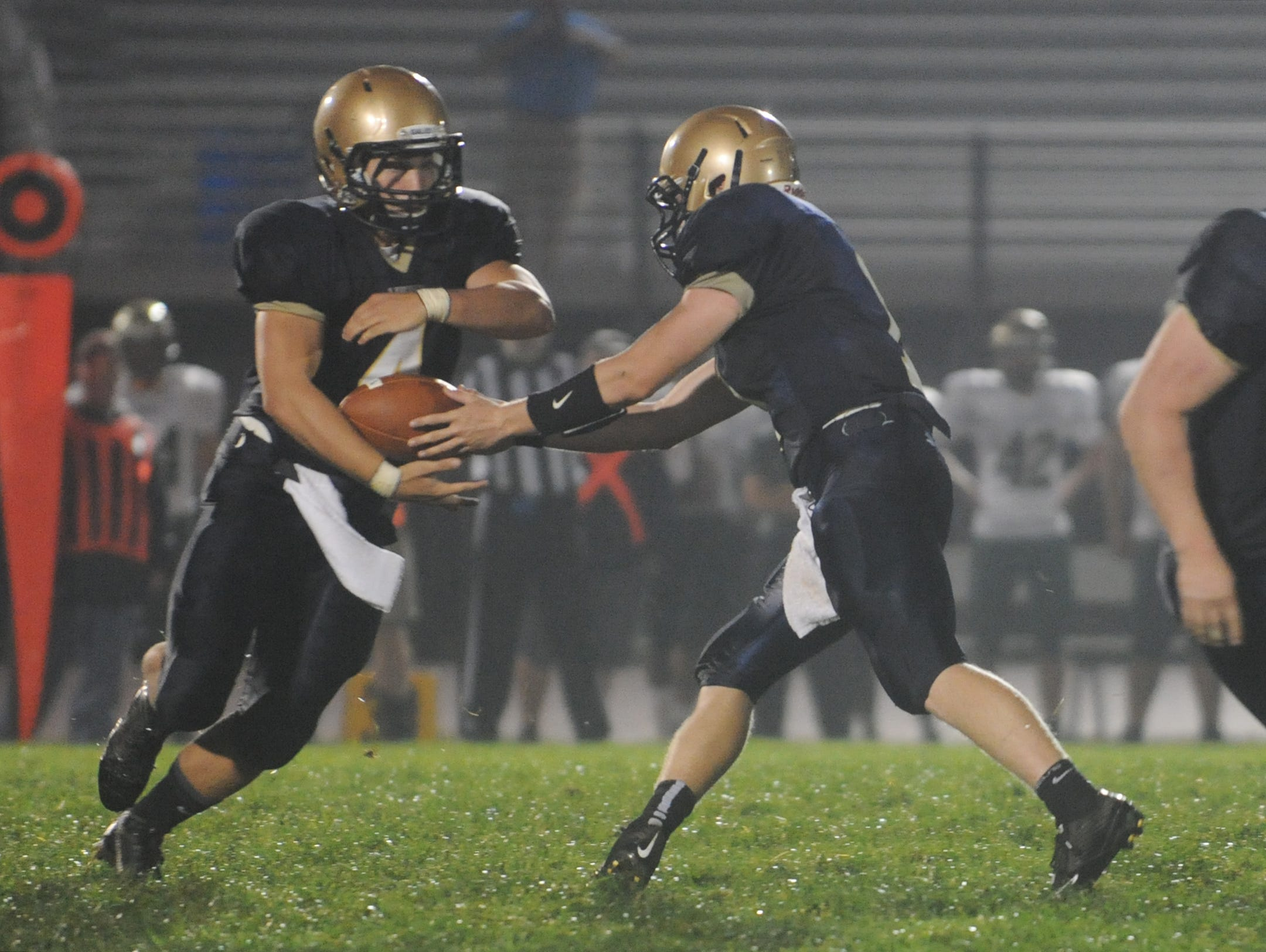 Lancaster's Noah Dryden, right, hands the ball off to Drew Smith during Lancaster's game against Dublin Jerome Friday, Sept. 4, 2015, at Fulton Field. The Gales defeated the Celtics 33-0.