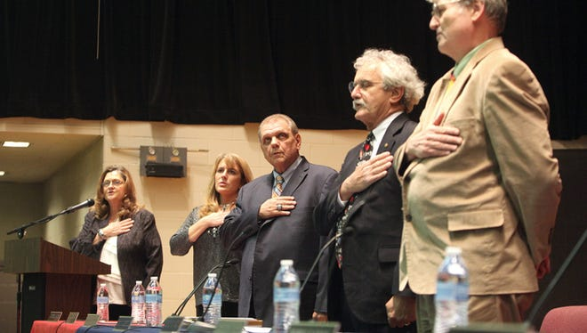 "School board members Andy Warrner and Tony Costello, right-to-left, and Superintendent Tim Heller ""Pledge Allegiance to the Flag"" at a meeting in 2013."