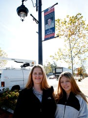 Lis Gessel of New City, along with her daughter, Victoria Richey stand near a banner placed on Main Street in New City that honors Gessel's service in the U.S. Army and her tour in Iraq on Nov. 10, 2016.