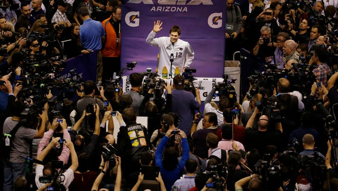 New England Patriots' Tom Brady waves during media day for NFL Super Bowl XLIX football game Tuesday, Jan. 27, 2015, in Phoenix.
