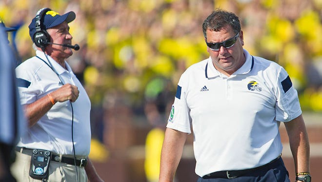 Michigan coach Brady Hoke walks the sidelines during the 30-14 loss to Minnesota today in Ann Arbor.