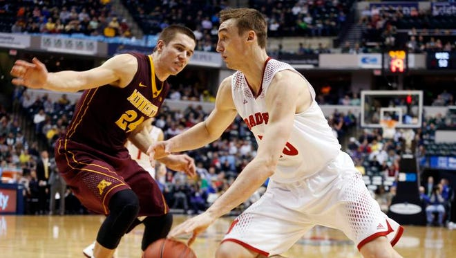 Wisconsin Badgers forward Sam Dekker (15) drives to the basket against Minnesota Golden Gophers forward Joey King (24) in the quarterfinals of the Big Ten college basketball tournament at Bankers Life Fieldhouse.
