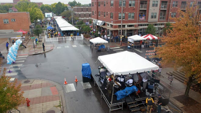 Patrons take shade from the rain at Oktoberfest on Saturday, Sept. 28, 2013.