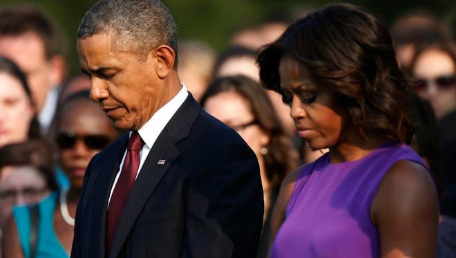 President Barack Obama and first lady Michelle Obama stand for a moment of silence on the South Lawn at the White House on Sept. 11, 2013, as they mark the 12th anniversary of the 9/11 terror attacks.