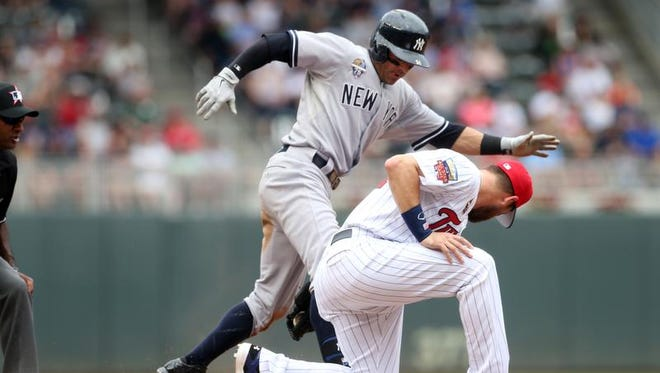 New York Yankees' Brian Roberts, right, beats the tag by Minnesota Twins' Trevor Plouffe to triple in the fourth inning of a baseball game, Friday, July 4, 2014, in Minneapolis.