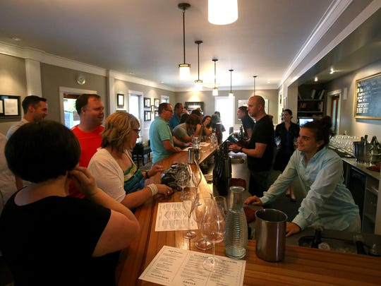 Carly O'Connell, right, talks with customers in the Argyle Winery tasting room in Dundee.