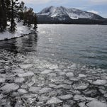 Ice chunks float at the end of Paulina Lake, with the view of Paulina Peak in the background.