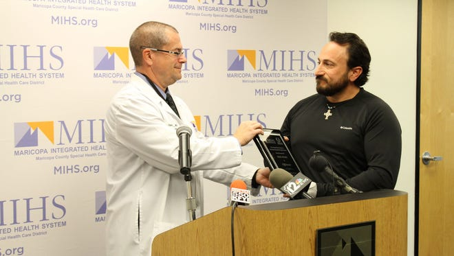 Cliff Faraci, right, receives a heroism award from Dr. Kevin Foster, Director of Maricopa Integrated Health System's Arizona Burn Center.
