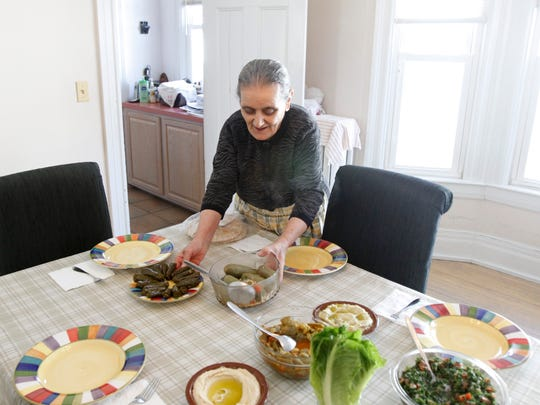 "Laurice Sarkis Mina puts dishes on the table. ""We have to fight with her to sit down and eat. She is always cooking,"" says her son, Sami Mina."