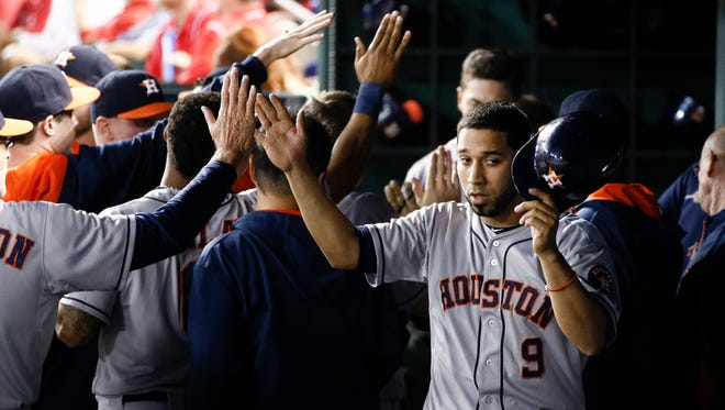 Marwin Gonzalez is congratulated by teammates after scoring the go-ahead run against the Rangers in the 10th inning.