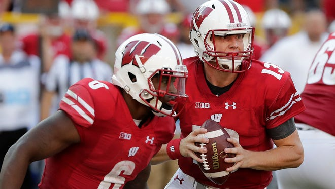 Wisconsin Badgers quarterback Bart Houston (13) looks to pass as running back Corey Clement (6) blocks against LSU at Lambeau Field Sept. 3, 2016.