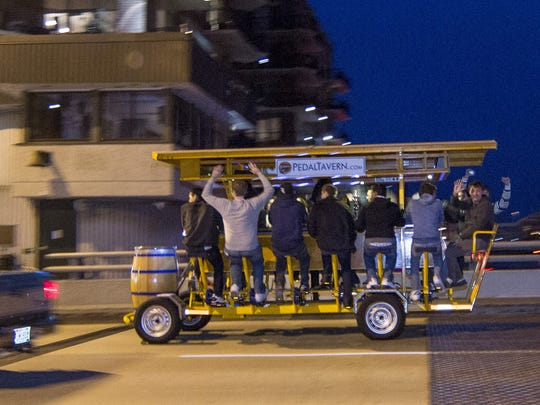 Riders on the popular Pedal Tavern travel along Water Street in the Third Ward on Oct. 5, 2012, in Milwaukee.