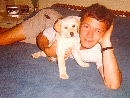 Roger Hartman holds his puppy, Bess.