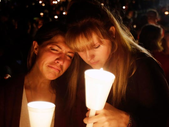 Kristen Sterner, left, and Carrissa Welding, both students at Umpqua Community College, embrace each other during a candlelight vigil for those killed during a shooting at the college, Thursday, Oct. 1, 2015, in Roseburg, Ore.