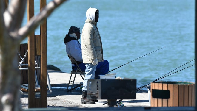 Fishermen bundle up by the water in Fort Pierce in February 2016.
