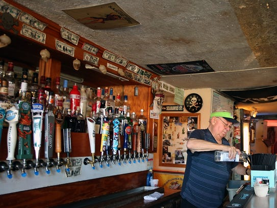 Owner Fred Lanouette pours a drink behind the bar of his Old Town Pub in Silverdale. Lanouette owns the bar but sold the building to the Port of Silverdale a year ago.