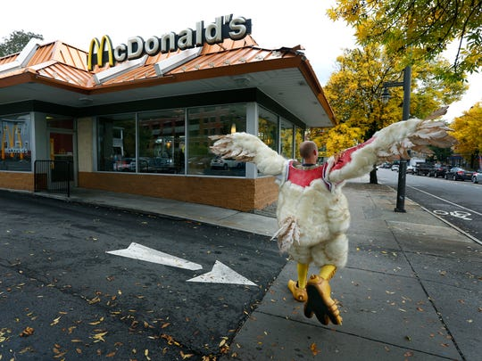 """Noah Church of Portland, Oregon, skips away with the """"Abby the Abused Chicken"""" costume after standing for an hour in front of the Monroe Avenue McDonald's."""