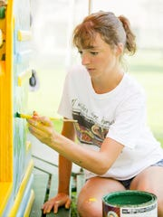 Julia John, a 2013 graduate of Ithaca High School, now a student at the Maryland Institute College of Art, paints one of the two chariot benches on the carousel Tuesday afternoon in Stewart Park.