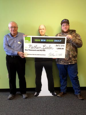 Nathan Bixler, right, a local winner of the H&R Block 1,000 Win $1,000 Daily Sweepstakes, is presented with a giant check from Tax Specialist William Setlak. They are shown with a cardboard stand-up of Richard Block, owner of H&R Block. They celebrated recently at the H&R Block office at 334 Lincoln Way East in New Oxford.