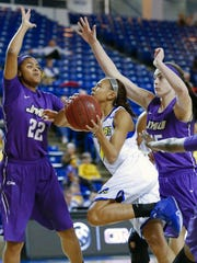 Delaware's Chastity Taylor (center) drives between James Madison's Aneah Young (left) and Savannah Felgemacher in the fourth quarter of the Blue Hens' 65-43 loss at the Bob Carpenter Center Wednesday.
