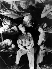 Ernie Pyle center talks with Marines below decks on a U.S. Navy transport en route to the invasion of Okinawa during World War II in this March 1945 file photo. Pyle was killed on April 18, 1945, by Japanese machine-gun fire on the island of Ie Shima in the southwestern Pacific Ocean near Okinawa.