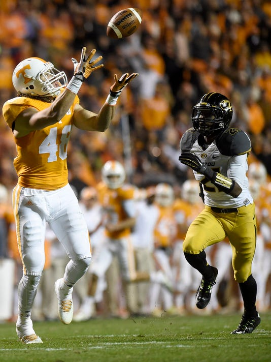 Tennessee tight end Alex Ellis (48) catches a pass on a fake field goal for a touchdown against Missouri safety Ian Simon (21) during the first half at Neyland Stadium on Saturday, Nov. 22, 2014, in Knoxville, Tenn.  Missouri won 29-21.  (AP Photo/Knoxville News Sentinel, Adam Lau)