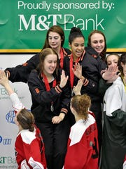 The second-place York Suburban 200-yard freestyle relay team greets the first-place Schuylkill Valley team during the medal ceremony for the 200-yard freestyle relay in the District 3 Class 2A girls swimming championships Friday, March 3, 2017, at Cumberland Valley High School.