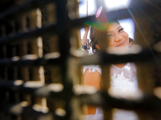 """In this Nov. 18, 2017, photo, Evelia Reyes looks into the United States at Friendship Park, part of Border Field State Park, through the border fence from the Mexico side, before getting married to Brian Houston at the """"Door of Hope,"""" part of the border fence between the U.S. and Mexico. A U.S. citizen, forbidden to enter Mexico, met and wed the her in a brief moment when the gate separating the two countries was opened. Now it turns out the groom is a convicted drug smuggler and border agents are furious that he passed a federal background check and was approved for the """"Door of Hope."""""""