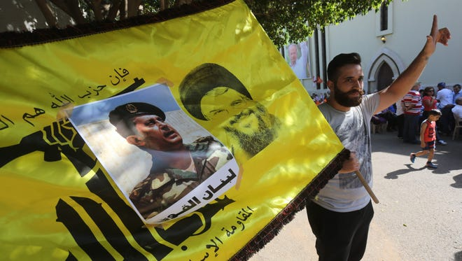 Supporters of Lebanon's Free Patriotic Movement celebrate the election of their leader MP Michel Aoun (portrait) and carry the flag of Shiite movement Hezbollah in the town of Jdeideh north of Beirut on Oct. 31, 2016.