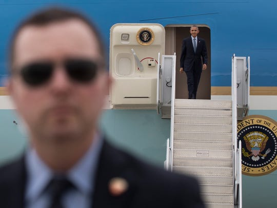 President Barack Obama exits Air Force One, as a member