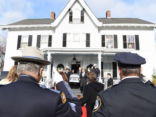 Officers salute the casket of retired Sheriff Fred Scoralick as it leaves McHoul's Funeral home in Hopewell Junction on Thursday.