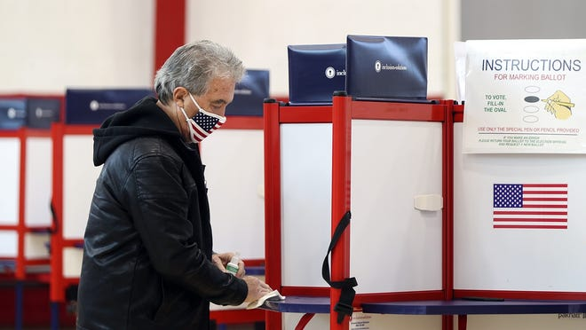 Stephen Mordas sanitizes a polling booth in between voters at the Bridgewater Middle School on Election Day, Tuesday, Nov. 3, 2020.