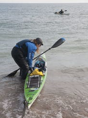 Traci Lynn Martin pulls her kayak into Lake Huron as