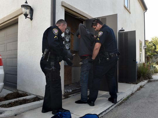 Oxnard police officers Jacob Jundef (left) and Greg Utter search a known drug user found sleeping in an electrical closet during a patrol in November.